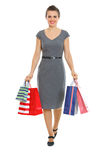 Female in dress walking with shopping bags Stock Images
