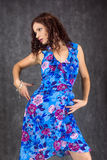 Female dressed in a blue dress. Pretty woman dressed in a blue dress with red flowers Royalty Free Stock Images