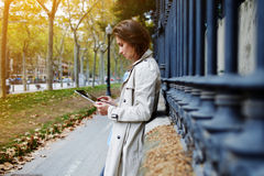 Female dressed in spring clothes is reading information in internet via digital tablet Stock Photo