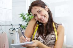 Female dressmaker taking notes while talking on telephone royalty free stock images