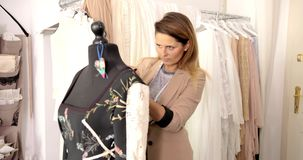Female dressmaker using mannequin in parlour stock footage