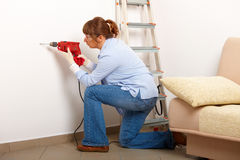 Female drilling hole. Beautiful woman working drilling hole in white wall in home, wearing protective  gloves and glasses, ladder in background Royalty Free Stock Image