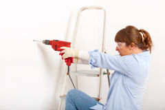 Female drilling hole. Beautiful woman working drilling hole in white wall in home, wearing protective  gloves and glasses, ladder in background Royalty Free Stock Photo