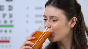 Female drinking delicious carrot juice, supplement for vision health, nutrition. Stock footage stock video footage