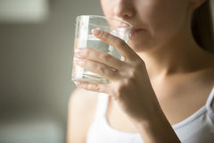 Female drinking from a glass of water. Health care concept photo, lifestyle, close up royalty free stock photography