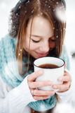 Female Drinking Hot Drink Outdoors in Winter. Young Beautiful Female Drinking Hot Drink Outdoors in Winter. Close Up Headshot. Drawn Snow. Selective Focus Royalty Free Stock Images