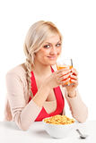 A female drinking a juice and eating cornflakes Stock Photo