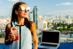 Female drinking orange cocktail from a straw, close-up stock photo