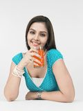 Female drinking orange juice Stock Image