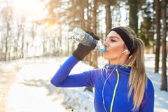 Female drinks water on break from running. In forest Royalty Free Stock Photos