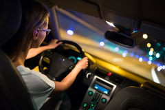 Female drive driving a car at night. Shallow DOF; colour toned image Royalty Free Stock Photography