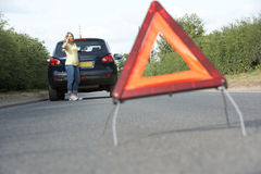 Female Driver Broken Down On Country Road. With Hazard Warning Sign In Foreground royalty free stock image