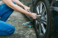 Female driver changing tyre on her broken car. royalty free stock image