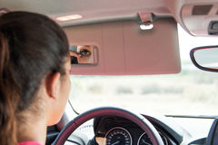 Female driver checking eye liner in car mirror Stock Photo
