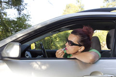Female driver doing make-up with red lipstick Stock Images