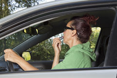 Female driver doing make-up with red lipstick Stock Photo