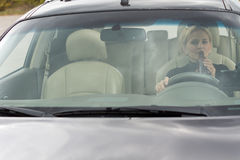 Female driver drinking alcohol in the car Royalty Free Stock Photos