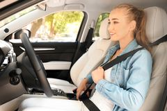 Female driver fastening safety belt. In car royalty free stock photography