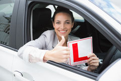 Female driver giving thumbs up while holding her L sign Royalty Free Stock Photo