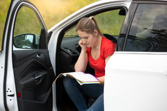 Female driver got lost while driving in countryside and reading. Young female driver got lost while driving in countryside and reading map to find the route Royalty Free Stock Photo