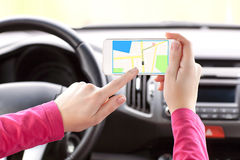 Female driver hand holding phone with interface navigator Royalty Free Stock Photo