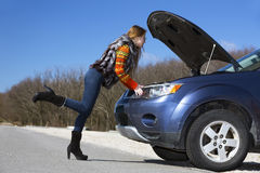 Female driver inspects her car engine Royalty Free Stock Photo