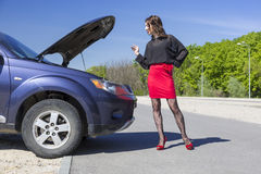 Female driver inspects her car engine Royalty Free Stock Image