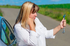 Female driver is looking at spanner Royalty Free Stock Image
