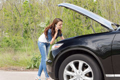 Female driver phoning for help after a breakdown Royalty Free Stock Images