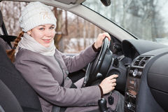 Female driver putting ignition key. And starting car Stock Photography