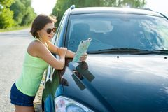 A female driver reading a map near a car. Female driver reading a map near a car Stock Photo