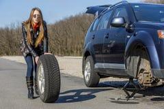 Female driver repairs car Royalty Free Stock Photos