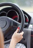 Female driver's hands on a steering wheel Stock Image