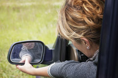Female driver. Setting a side mirror of a car, outdoor shot, concept of safe driving Royalty Free Stock Image
