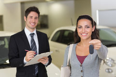 Female driver showing a key after bying a new car Stock Image