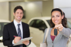 Female driver showing a key after bying a new car Royalty Free Stock Photos