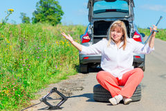 Female driver sitting at the wheel near the broken car Royalty Free Stock Photos