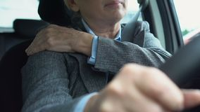 Female driver in suit massaging painful shoulder in car, sedentary lifestyle