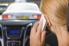 Female Driver Talking On Phone Whilst Driving stock photography