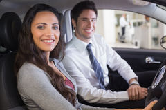 Female driver at the wheel sitting in her car with salesperson Stock Image