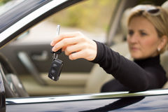 Female drivier holding out the car keys Royalty Free Stock Photo