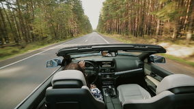 Female driving a luxury open top car stock footage