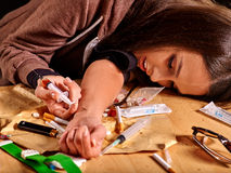 Female drug addict with syringe in hand. Female drug addict with syringe on his arm lying at table royalty free stock image