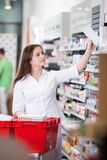 Female at drugstore. Female pharmacist keeping medicine box on the shelf at drugstore royalty free stock images