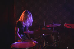 Female drummer performing on illuminated stage Royalty Free Stock Image