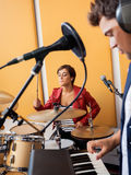 Female Drummer Performing With Male Pianist. Young female drummer performing with male pianist in recording studio Royalty Free Stock Images