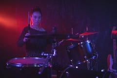 Female drummer playing drum kit in illuminated nightclub Royalty Free Stock Photos