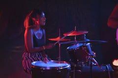 Female drummer practicing in nightclub Stock Image