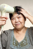 Female drying her hairs Royalty Free Stock Photography