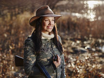 Female duck hunter. Waterfowl hunting, the female hunter carry a shotgun, autumnal bushes on background stock images